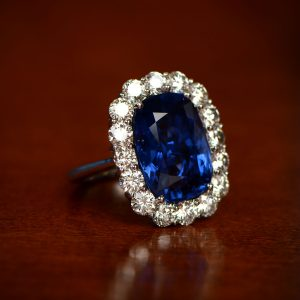Sapphire Ring with Diamond Halo on Brown Table Dini Berger