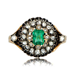 an emerald engagement ring framed by a halo of diamonds.