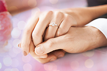 close-up shot of a couple holding hands featuring an engagement ring.