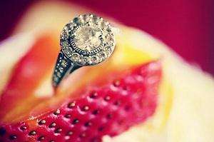A vintage engagement ring nestled in a strawberry cookie
