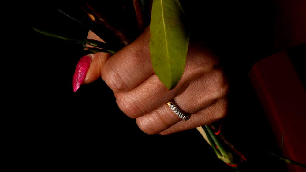 Holding flowers with wedding ring