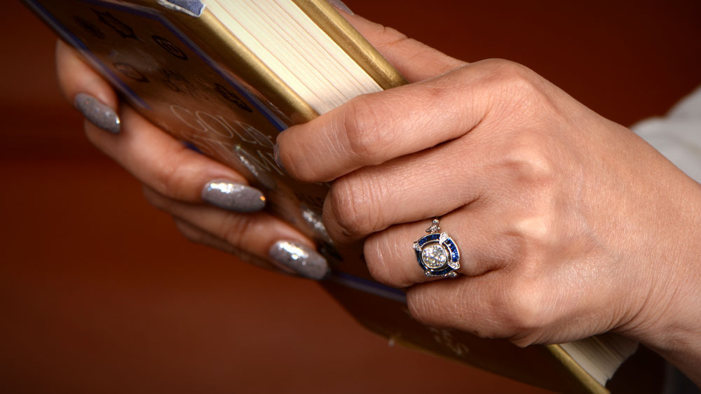 girl holding book while wearing engagement ring