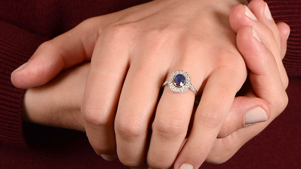 Wearing a oval cut sapphire ring with diamond halo